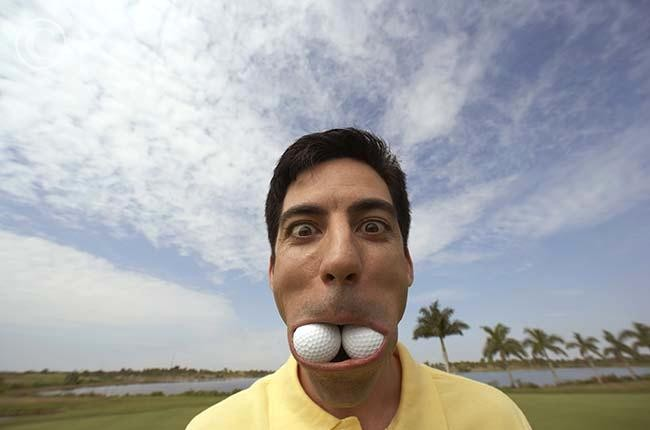 Hispanic man with golf balls in mouth